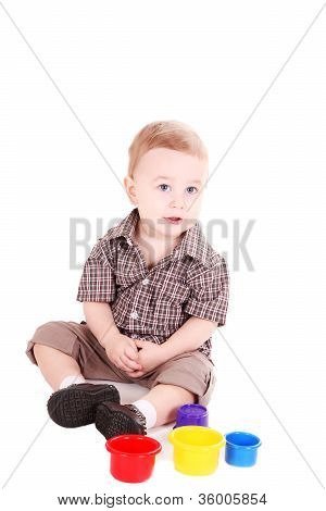 little boy in a checkered shirt with plays bright toys