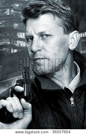 Portrait of the serious unshaven man with pistol.