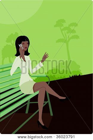 Businesswoman Talking On Her Cell Phone While Sitting On A Park Bench