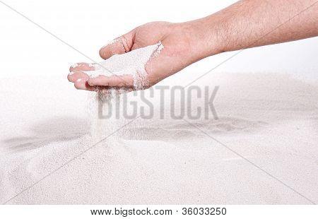 sand runs through hand
