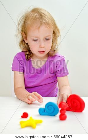 Liitle Girl Learning To Use Plasticine