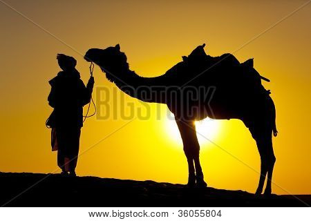 Rajasathan village man holds his camel.