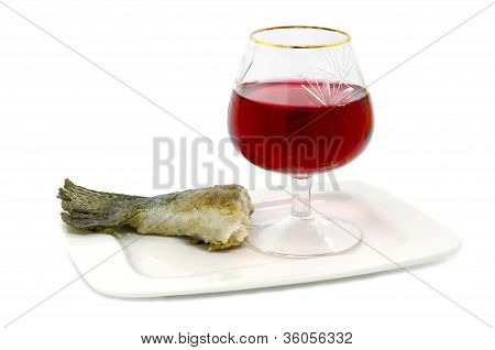 fish tail and glass of red wine isolated on white background