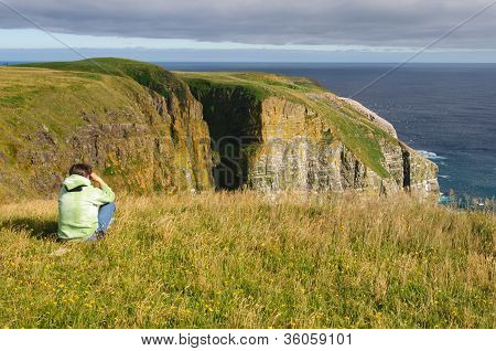 Birdwatcher Looking At Birds On Coastal Cliffs