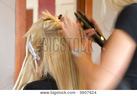Hairdresser Applying Extensions To Client'S Hair
