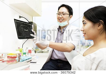 Asian Dentist With X-ray And Patient