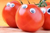 picture of googly-eyes  - Funny tomatoes with googly eyes on orange background - JPG