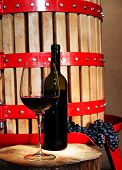 image of wine-press  - Still life with glass of red wine and vintage wine press in the background - JPG