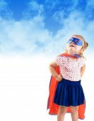 pic of superwoman  - A young girl is dressed up as a superhero and looking up in the sky with a mask and cape - JPG