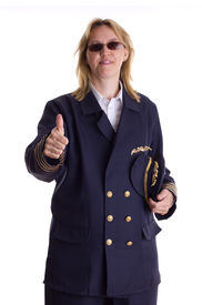 stock photo of stewardship  - Female pilot showing thumbs up sign and holding her cap in her hand - JPG