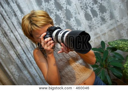 Woman Holding And Looking Into A Professional Camera