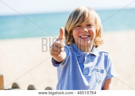 Garoto loiro bonito fazendo os polegares para cima na praia.