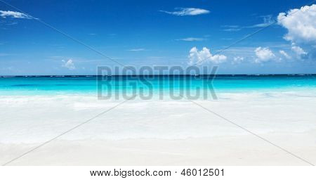 Beautiful seascape, clean turquoise sea, white sandy coastland, blue sky, exotic beach, luxury resort, summer vacation and holiday concept