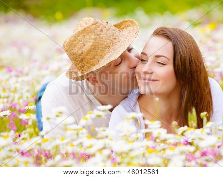 Two happy lovers laying down on white floral meadow, handsome guy kissing his cute girlfriend, relaxation outdoor, romance concept