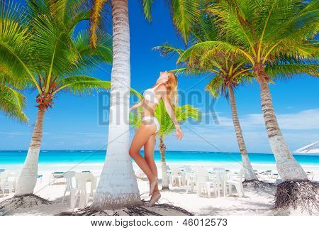 Sexy blond woman on the beach wearing bikini, enjoying summer holidays, tropical exotic escape, people getaway, luxury spa and travel concept