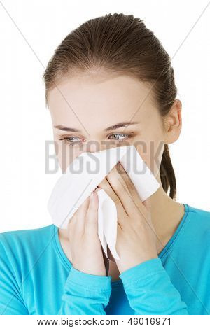 Young woman with tissue - sneezing. Allergy or cold. Isolated on white.
