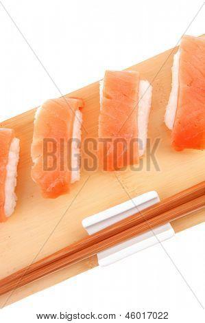 Nigiri Sushi - Set of Nigiri sushi topped with raw Salmon . isolated over white background . on wooden board