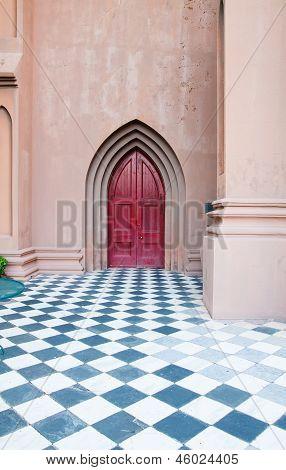 Red Church Door Beyond Checkerboard Patio
