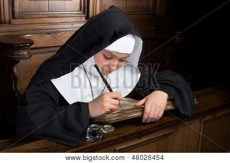 Young nun writing in an ancient book in a medieval church interior