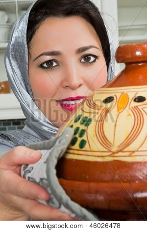 Traditional Moroccan immigrant woman in Europe cooking tajine during Ramadan in her modern kitchen