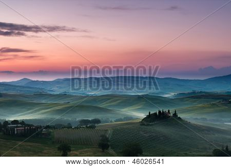 White fog and purple clouds on a beautiful morning in the Tuscan hills near Pienza