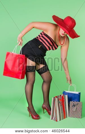 Sexy pin up girl holding paper shopping bags
