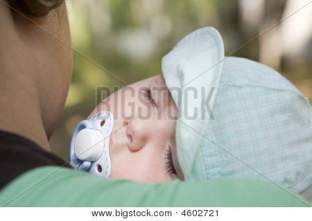 One-year-old Baby Sleeping On Shoulder Of Mother