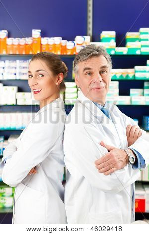 Two Pharmacists standing in pharmacy or drugstore in front of shelves with pharmaceuticals