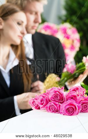 Mourning man and woman on funeral with pink rose standing at casket or coffin
