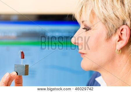 Older woman or female pensioner with hearing problem taking a hearing test, she holding model of hearing aid