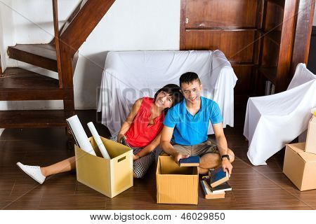 Real estate market - Young Indonesian couple moving in a home or apartment, they are sitting on the floor and having a break