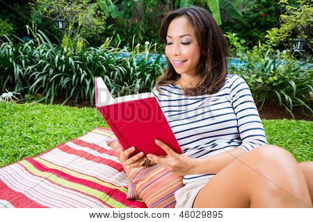 Young Indonesian woman lying at home in the garden and reading a book in her leisure time