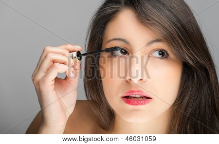 Portrait of a beautiful woman applying makeup