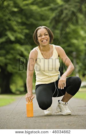 Woman kneeling on water bottle in park