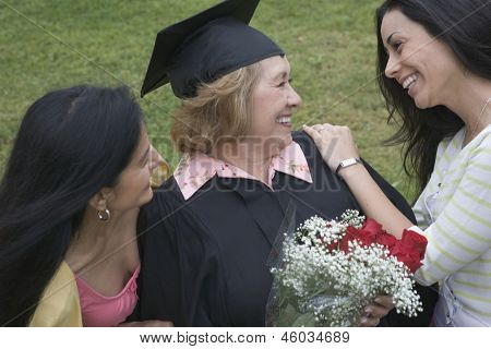 Older graduate receiving praise from family