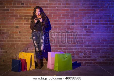 Pretty Mixed Race Young Adult Woman with Shopping Bags Using Her Cell Phone Against a Brick Wall - Plenty of Copy Space.