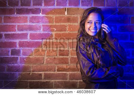 Portrait of a Pretty Mixed Race Young Adult Woman Using Her Cell Phone Against a Brick Wall with Plenty of Copy Space.