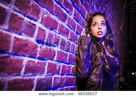 Frightened Pretty Young Woman Against a Brick Wall at Night.