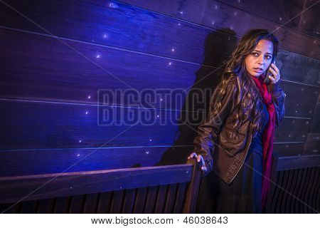 Frightened Young Woman in Dark Walkway Using Cell Phone at Night.