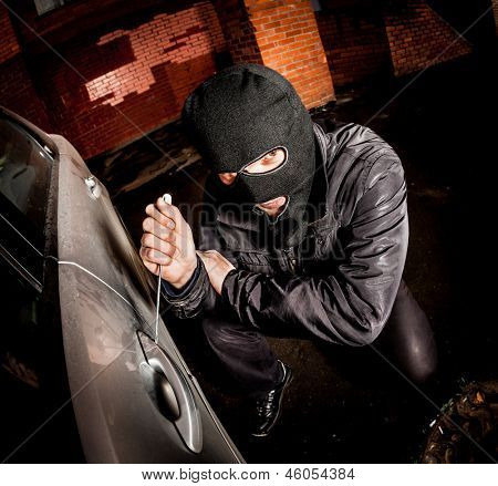 Robber and the car thief in a mask opens the door of the car and hijacks the car.