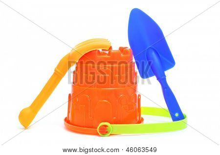 closeup of a sand / beach toy set with a pail, shovel and rake of different colors on a white background