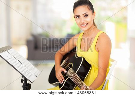 cute young woman practicing guitar at home