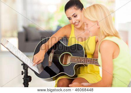 pretty music teacher tutoring young girl to play guitar