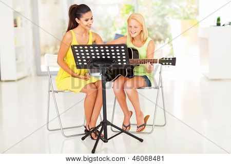 happy preteen girl having guitar lesson with music tutor at home