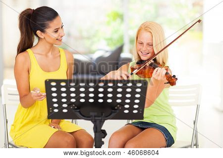 beautiful music teacher tutoring young girl to play violin