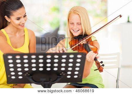 cheerful pre teen girl enjoying her violin lesson with music teacher at home
