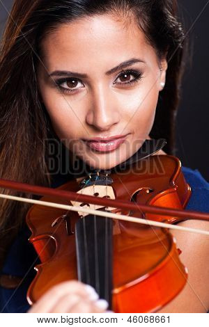 portrait of beautiful violinist over black background