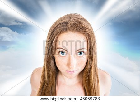 Fantasy portrait of a young woman with striking blue eyes, against a blue sky and cloud background with a dreamy light effect.