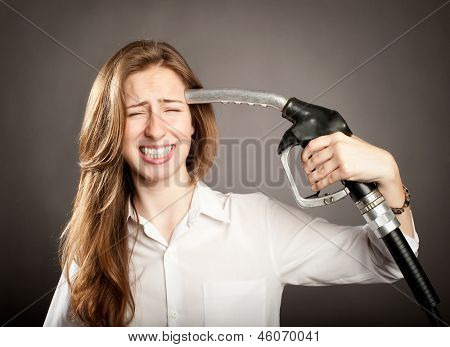 young woman shooting herself with a fuel pump nozzle