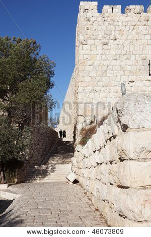 Two religious Jews in traditional clothes go along the Jerusalem wall